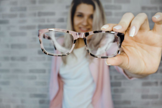 lady holding her spectacle lenses in front of her