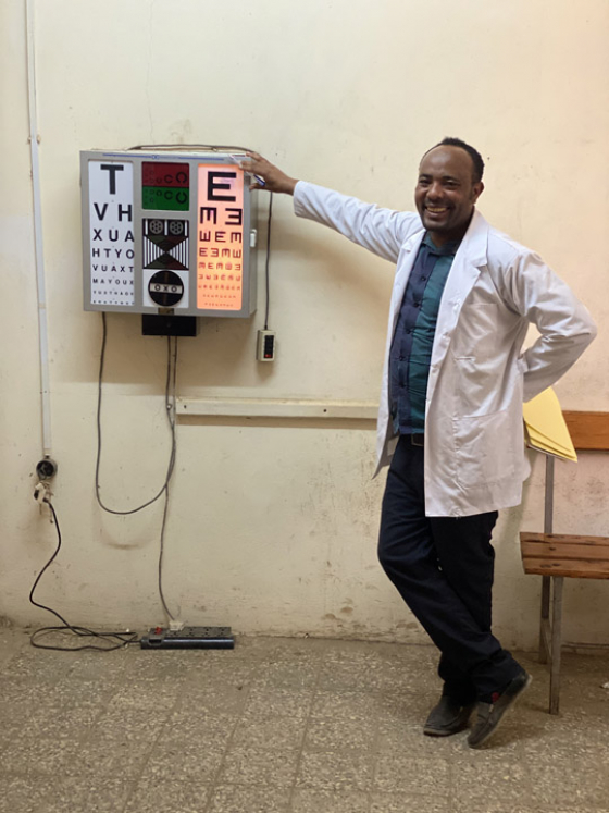 An optician in Ethiopia stood next to eye examination chart