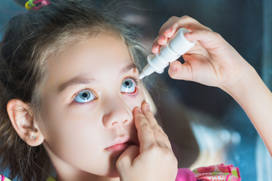 Young girl using eye drops to treat an eye infection