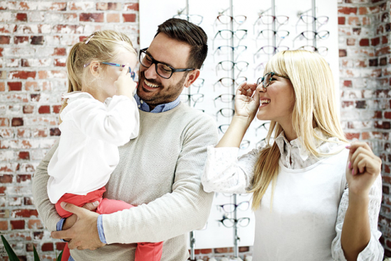 Family at the opticians trying on glasses