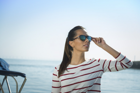 Woman wearing polarised lenses stood on a boat looking in the distance