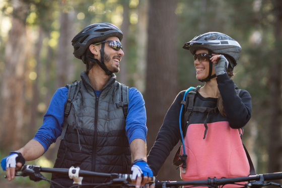 Man and woman wearing sunglasses riding bikes